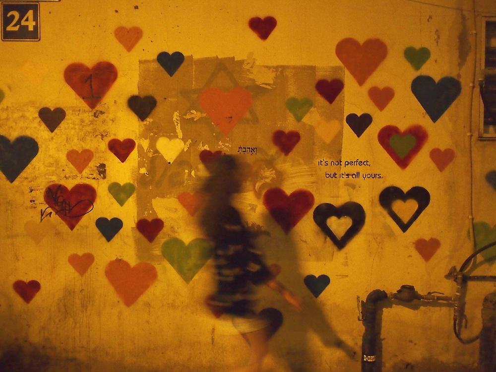 A girl walks by a wall of street art in Tel Aviv, 2013.