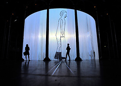 © licensed to London News Pictures. LONDON, UK.  08/08/11. People watch Animation Stills from Walker by David Shringley. Ron Arad's Curtain Call opens at the Roundhouse, Camden in London today (9th August 2011). Arad has installed a huge light curtain made of 5,600 silicon rods, suspended from an 18 metre diameter ring. Films, live performance and audience interaction can all take place within and around the rods. Mandatory Credit Stephen Simpson/LNP