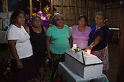 Friends and family pose for a photograph inside La Joya's chapel along with the coffin containing the human remains of massacre victim Teodora Ramirez. From left to right: Victoria Sánchez, 68, Antonia Ramirez (victim's daughter), 60, Elia Ramirez (victim's daughter), 55, Dionisia Sánchez Ramirez, 59, and Rosario Lopez Sánchez, 70. The massacre at La Joya is one of six mass killings that took place in villages within the municipality of Meanguera from Dec. 11-13, 1981, by the US-trained Atlacatl Battalion of the Salvadorian Armed Forces, left over 900 civilian victims and are known collectively as the Massacre at El Mozote and surrounding villages. Earlier in 2016, an amnesty law signed after the 1992 Peace Accords that prevented war crimes from being investigated and tried was lifted by El Salvador's Supreme Court, allowing cases like El Mozote to proceed legally against its perpetrators. La Joya, Meanguera, Morazan, El Salvador. December 10, 2016.