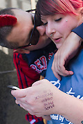 "October 16, 2010 - Boston, MA - Simon West kisses Lindsay Gregory while she reads a text messaged clue on her cell phone during the Boston Diamond Dash, a city-wide scavenger hunt for a $20,000 Ritani diamond ring from Long's Jewelers. West and Gregory say they are unofficially engaged, waiting until they can afford a ring before he gets on one knee.  ""Who needs a $20,000 ring?"" said West, an Englishman from Nottingham who is in the United States on a three-month visa. ""We'll definitely sell it, buy a ring, and use the rest to help me stay in the states."" (Photo by Amy Donnelly, COM 2011)"