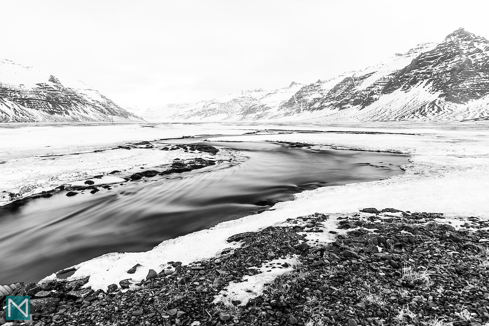 A river flows through snow-covered Steinasandur in southern Iceland