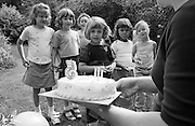 As her mother carries out a specially-baked cake with candles to blow, a young girl celebrates her fifth birthday with close friends in her back garden at home.