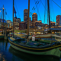 Sail Boston tall ship Essex moored at Fan Pier in the Boston Harbor with waterfront skyline photography from New England photographer Juergen Roth. The image shows the historic sailboat in front of the Boston Financial Waterfront District landmarks such as the Custom House of Boston, One International Place, Boston Harbor Hotel photographed on a beautiful summer sunset evening. <br />