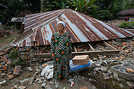 Tanjung, Western Sumatra, Indonesia, 8th October 2009: A woman who has just received a tarpaulin and Hygiene pack from international aid agency Save the Children stands in front of her heavily damaged house after the devastating earthquake in Western Sumatra that claimed the lives of an estimated 2000 people.?photo: Joseph Feil