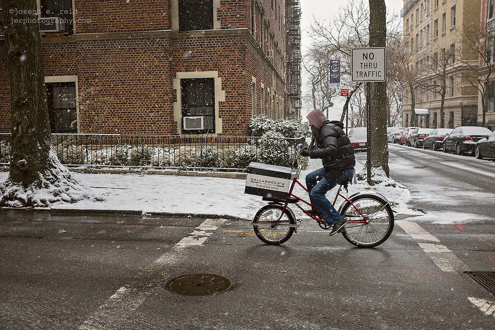 Pizza delivery man on bicycle during snowstorm, Brooklyn, NY, US