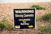 Sign warning of strong currents water unsuitable for bathing, Shingle Street, Suffolk, England