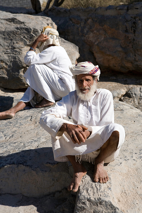 Two elderly men seated in the Omani village of Misfah.  They wear traditional Omani dress of dishdasha and turban.