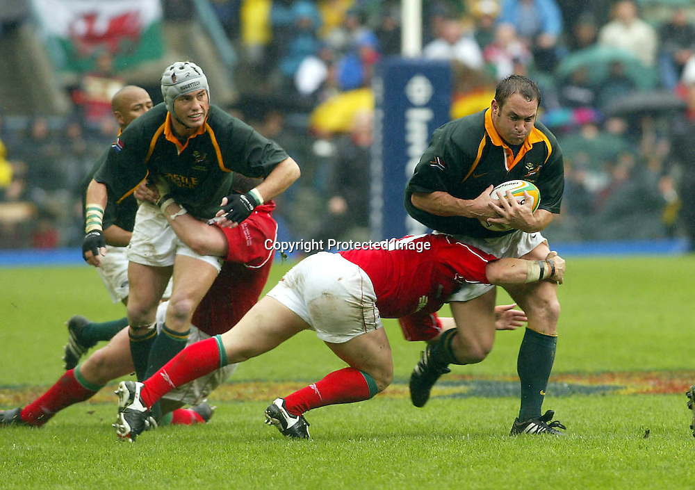 15/06/2002 Springboks vs Wales at Newlands Cape Town - Spring boks won 19-8 - Faan Rautenbach on the attack with Stephen Jones doing the tackling.<br /><br />Credit:PHOTOSPORT