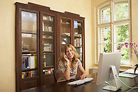 Young woman using mobile phone in front of computer in living room