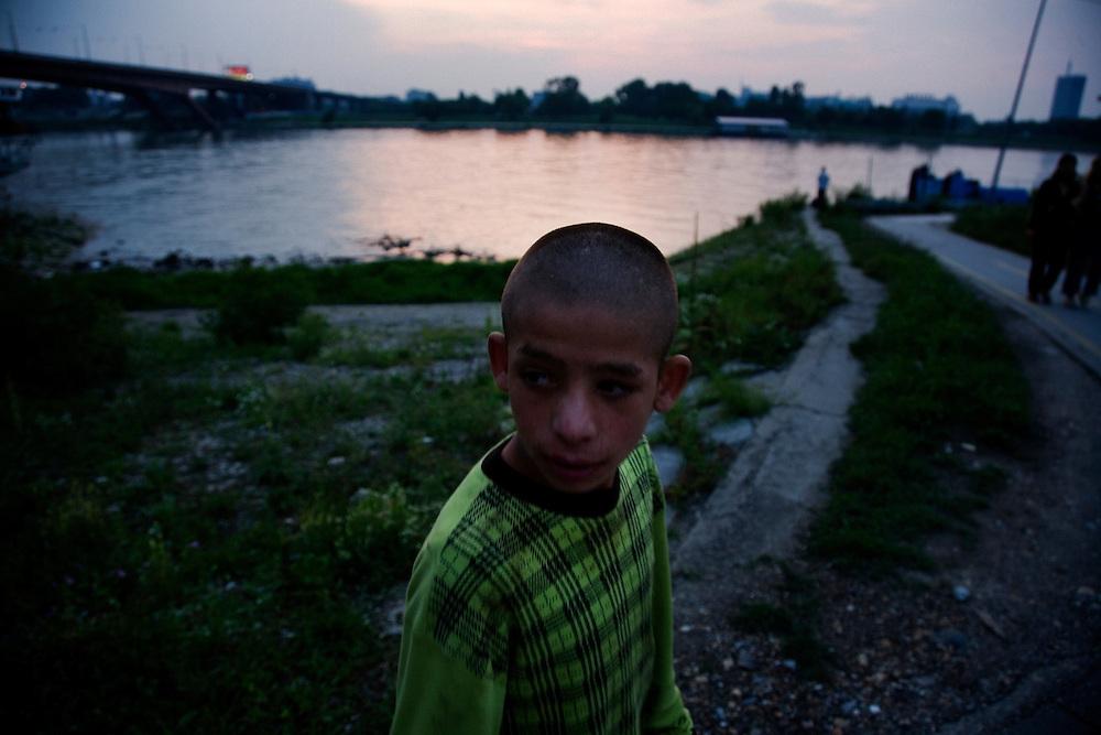 A boy walks along the Sava River near the Stara Gazela camp.