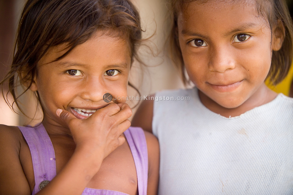 Two young Miskito girls smile for the camera in the remote indigenous village of Krin Krin, Nicaragua, on the Rio Coco. Residents along the Rio Coco were considered Contra allies during the war, and were forced to evacuate in masses when their crops and homes were burned by Sandinista government military. After they were allowed to return, Hurricane Mitch hit them in 1998, which flooded the river to around 30 feet above normal. Residents continue to struggle to make a livelihood.