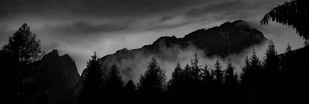 Molveno Storm. Italy. A black and white photograph of storm clouds, trees, and mountians over Molveno, Italy.