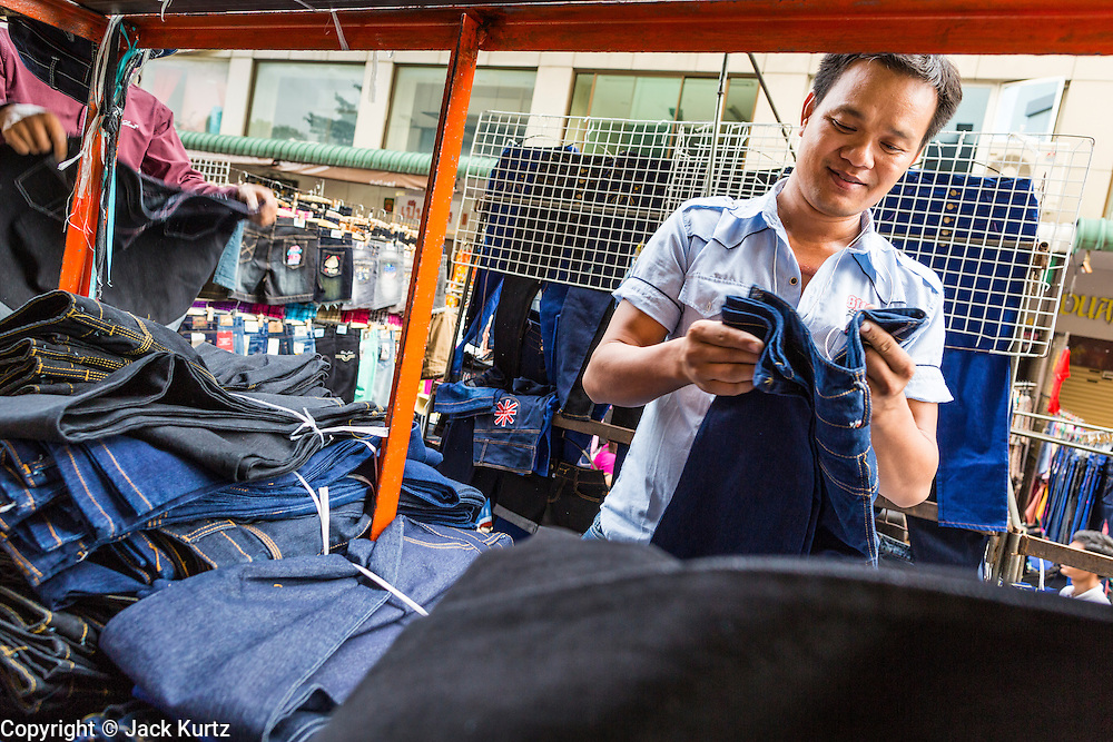 06 JUNE 2013 - BANGKOK, THAILAND:     A blue jeans vendor folds jeans in his market stall in Bobae Market in Bangkok. Bobae Market is a 30 year old market famous for fashion wholesale and is now very popular with exporters from around the world. Bobae Tower is next to the market and  advertises itself as having 1,300 stalls under one roof and claims to be the largest garment wholesale center in Thailand.       PHOTO BY JACK KURTZ