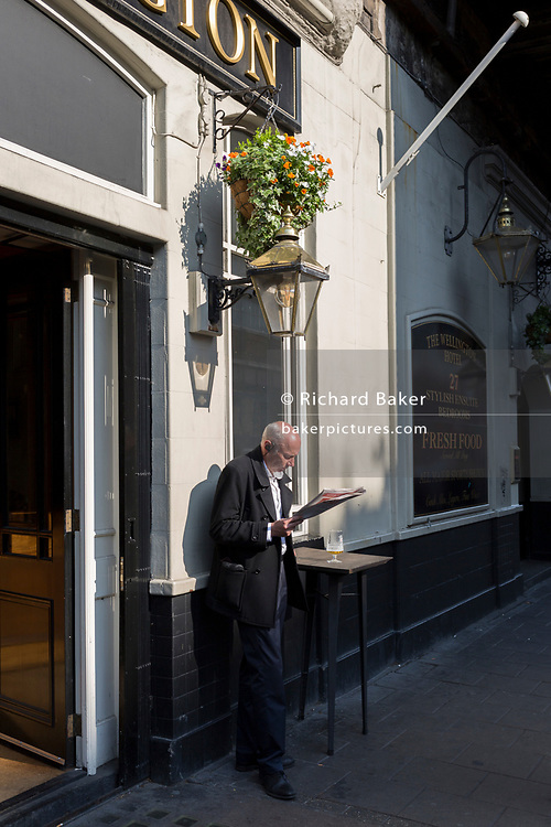 A man reads a copy of the free Evening Standard  newspaper while enjoying after noon sunshine and a quiet beer outside the Wellington pub in Waterloo, on 1st April, 2019, in London England.