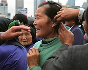 Shanghai, capitale e?conomique de la Chine, attire des touristes de partout dans le monde mais e?galement de toutes les re?gions de Chine. Cette femme qui visitait la ville avec son groupe ethnique se faisait placer les cheveux avant de se faire photographier devant les rutilants gratte-ciels de Pudong, le nouveau quartier ultra-moderne de Shanghai..