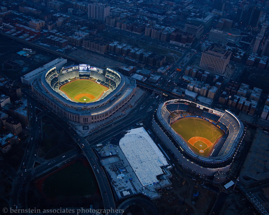 An aerial photograph of the new and old Yankee Stadiums lit up together for the last time.
