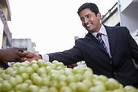 Business man paying fruit merchant low angle view