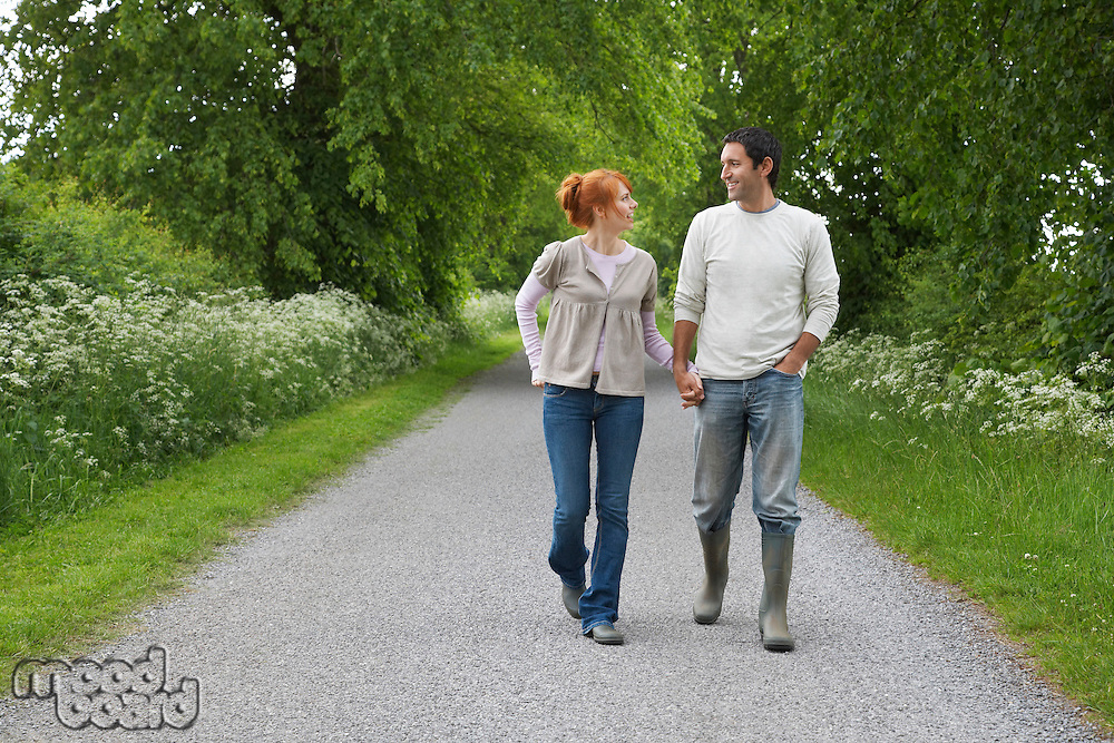 Couple holding hands walking on country lane