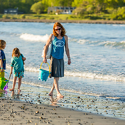 A woman walks with her young son and daughter at Seapoint Beach in Kittery, Maine.