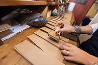 Cropped image of salesperson stamping paper bags at coffee store