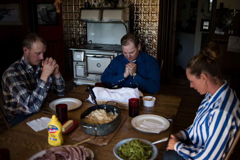 Riley Cihak, left, and Eric and Mindy Arneson pray before lunch on the Arneson ranch on the old abandoned town of Chance, SD on October 5, 2017. Eric Arneson moved his ranch from Montana many years ago due to rising land prices from wealthy people buying homes and land for hunting and vacation spots, forcing many local ranchers out.