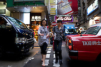 Two women crossing the Wellington street in Central, Hong Kong.