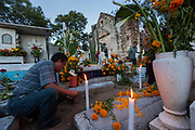 A Mexican man lights a candle at the gravesite of relatives for Day of the Dead festival known in Spanish as Día de Muertos at the old cemetery October 31, 2013 in Xoxocotlan, Mexico.  The festival celebrates the lives of those that died.