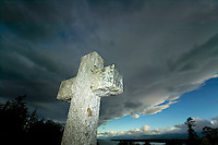A cross photographed from a low angle becomes a  monolith against a dramatic sky in Comox.  Comox, The Comox Valley, Vancouver Island, British Columbia, Canada.