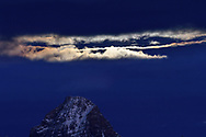 Bright clouds of the light of a super blue full moon over the mount Tinzenhorn at late dusk, Savognin, Parc Ela, Grisons, Switzerland