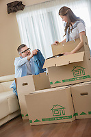 Couple unpacking cardboard boxes in new house