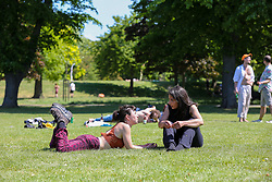 © Licensed to London News Pictures. 20/05/2020. London, UK. Members of the public relax in Markfield Park, Tottenham, north London on a warm and sunny day in London. The government has relaxed the rules on the COVID-19 lockdown, allowing people to spend more time outdoors whilst following social distancing guidelines. According to the Met Office, 27 degrees celsius is forecast for today.  <br /> <br /> ***Permission Granted***<br /> <br /> Photo credit: Dinendra Haria/LNP