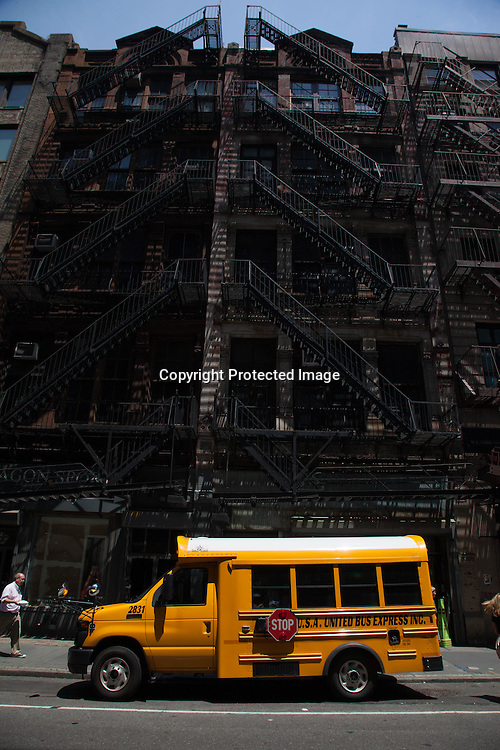 New York yellow school bus in front of a building with saircade on 18th street Manhattan