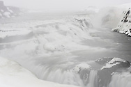 The waterfall Gullfoss of the river Hvita with ice formations on a fogy, cloudy day in the winter, vally Haukadalur, Iceland