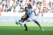 Swansea city's Jonathan De Guzman is challenged by Wigan's Jean Beausejour. Barclays Premier league, Swansea city v Wigan Athletic at the Liberty Stadium in Swansea, South Wales on Saturday 20th October 2012. pic by Andrew Orchard, Andrew Orchard sports photography,