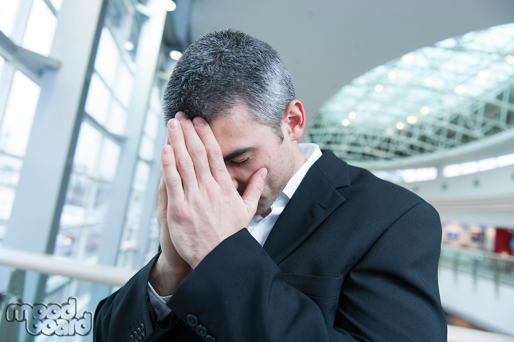 Disappointed businessman with head in hands