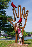 "Sisters Alayna and Faith Bond from Franklin, MA meandering through Meredith stop at ""Bird in Hand"" by Dale Rogers of Haverhill, MA as part of the Sculpture Walk on Sunday afternoon.  (Karen Bobotas/for the Laconia Daily Sun)"