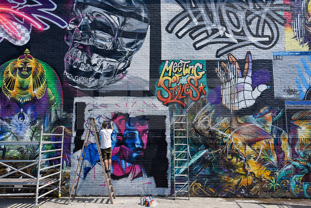 """© Licensed to London News Pictures. 28/05/2018. LONDON, UK. Core246, a street artist, at work at """"Meeting of Styles"""" near Brick Lane in East London.  The three day festival celebrates street art, with artists from around the world demonstrating their skills.  Photo credit: Stephen Chung/LNP"""
