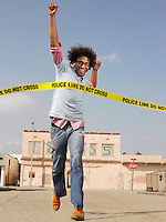 Young man crossing police tape in street