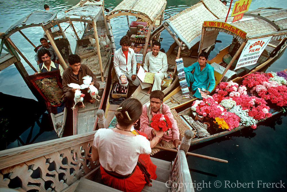 INDIA, KASHMIR Srinagar; vendors in their shakaras talking  to a customer on the porch of her rented  houseboat on Dal Lake