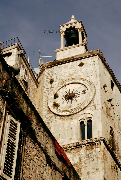 View of a medieval - Renaissance belltower in a residential area of Diocletian's Palace.  Medieval clock with Roman numerals around its circumference; bell in a loggia above; TV aerial visible from an adjoining residence.