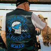 Member of 'Unknown Locos' motorcycle club wearing insignia waistcoat with a skull on the back, USA 1990's