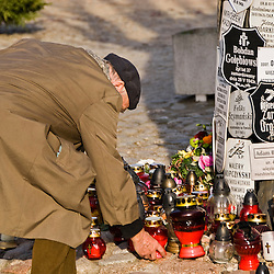 "Man putting candles on the memorial of the Holocaust during ""All Saint´s Day"" celebration, Warsaw, Poland, Europe."