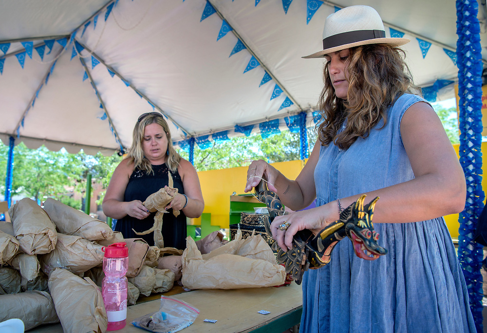 em071217d/b/Julie Ruth, left, and Aleishall Girard Maxon, both from Santa Fe, unwrap items to be sold in the Ambiance tent at the 2017 International Folf Art Marker on Museum Hill in Santa Fe. They were among around 2000 volunteers that are helping with the market this year. The Ambiance tent sells items that are used to decorate Museum Hill for the markter and the money raised goes to supporting the International Folk Art Market. The event starts Thursday and runs through the weekend but the main public events are Saturday and Sunday with 160 artist from 53 countries. Photo shot Wednesday July 12, 2017.  (Eddie Moore/Albuquerque Journal)