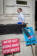 A man emerges from the Cabibet Office and passes Brexit protest placards outside the Cabinet Office on Whitehall, the location of daily Brexit contingency planning meetings (codenamed Yellowhammer, in government departments), on 19th August 2019, in London, England.