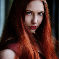 Close up of young adult female with long red hair wearing a red dress looking at camera