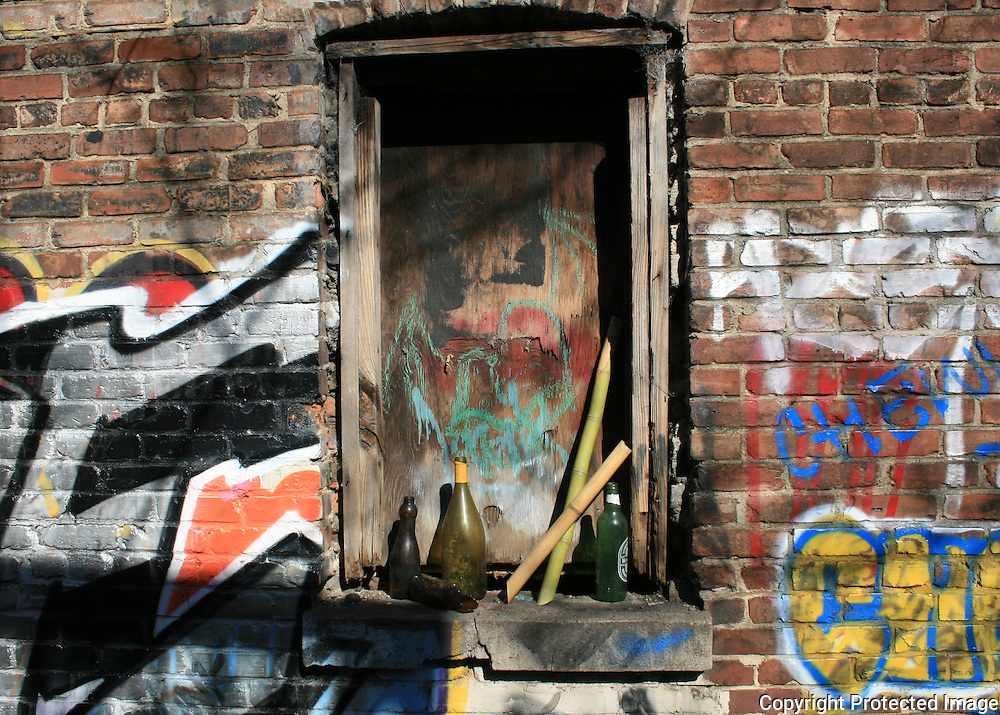 A boarded up window with assorted old bottles on the sill, on an abandoned building covered with grafitti.