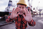 Caucasian stevedore talking to and gesturing at camera