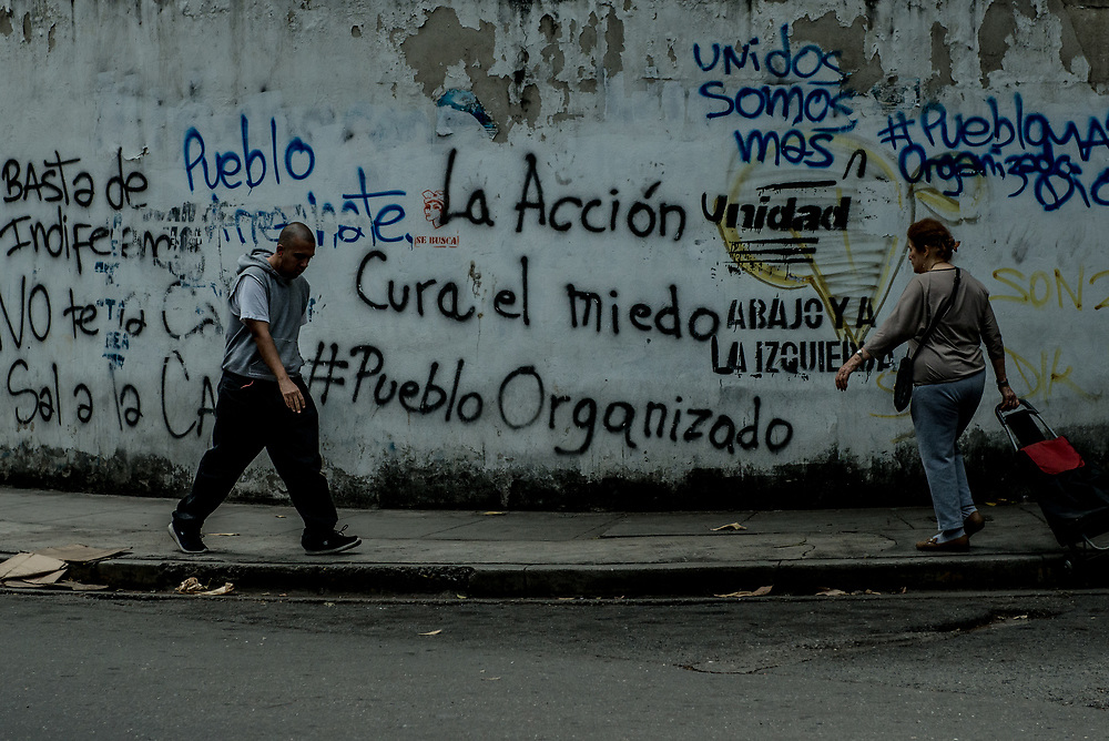 "CARACAS, VENEZUELA - APRIL 19, 2017:  People walk past anti-government graffiti in Caracas that says, ""Action cures fear"" and ""Stop the Indifference"" in Spanish.  PHOTO: Meridith Kohut"