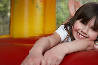 Girl (7-9) lying down in bouncy castle portrait close up