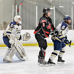 """FORT FRANCES, ON - May 1, 2015 : Central Canadian Junior """"A"""" Championship, game action between the Fort Frances Lakers and the Toronto Patriots, semi-final game of the Dudley Hewitt Cup. Mason Meyer #9 of the Fort Frances Lakers gets between Tyler Currie #4 of the Toronto Patriots and goaltender Mathew Robson #20 of the Toronto Patriots during the first period.<br /> (Photo by Shawn Muir / OJHL Images)"""